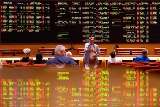 (AP Photo/John Locher). People sit in the sports book at the South Point hotel-casino, Monday, May 14, 2018, in Las Vegas. The Supreme Court on Monday gave its go-ahead for states to allow gambling on sports across the nation, striking down a federal l...