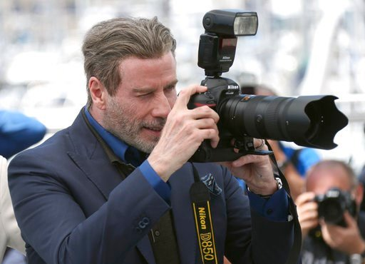 (Photo by Joel C Ryan/Invision/AP). Actor John Travolta takes a picture with a press photographers camera during the photo call for the film 'Gotti' at the 71st international film festival, Cannes, southern France, Tuesday, May 15, 2018.