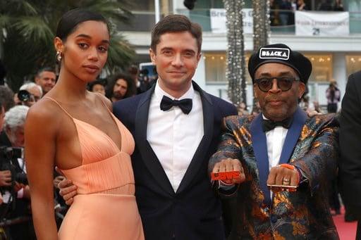 """(Foto por Vianney Le Caer/Invision/AP). La actriz Laura Harrier, el actor Topher Grace y el director Spike Lee posan al llegar al estreno de la película """"BlacKkKlansman"""" en el Festival de Cine de Cannes, el lunes 14 de mayo del 2018 en Cannes, Francia."""