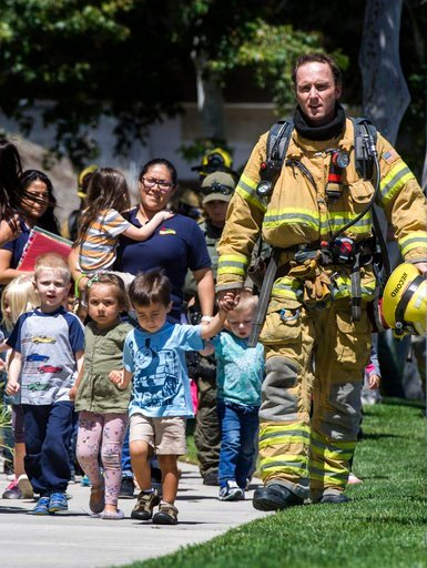 (Mindy Schauer/The Orange County Register/SCNG via AP). Firefighters and sheriff's deputies escort children from Academy on the Hill pre-k school in Aliso Viejo, Calif., on Tuesday, May 15, 2018, after a fatal explosion nearby. The blast involved a bui...