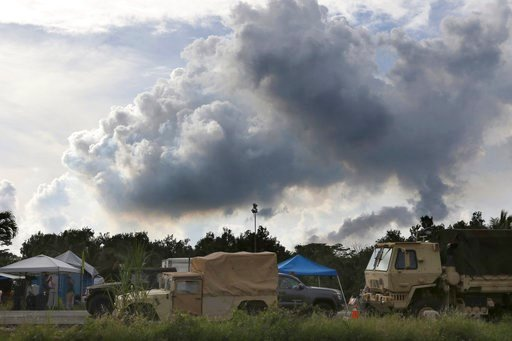 (AP Photo/Caleb Jones). With members of the National Guard in the foreground, volcanic gases rise from active fissures near Pahoa, Hawaii on Tuesday, May 15, 2018. Most of the nearby Hawaii Volcanoes National Park remains closed to visitors due to ongo...