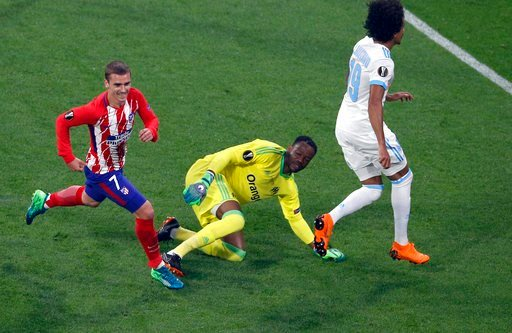 (AP Photo/Christophe Ena). Atletico 's Antoine Griezmann, left, runs as Marseille's goalkeeper Steve Mandanda, center, looks on after Griezmann scored his side opening goal during the Europa League Final soccer match between Marseille and Atletico Madr...