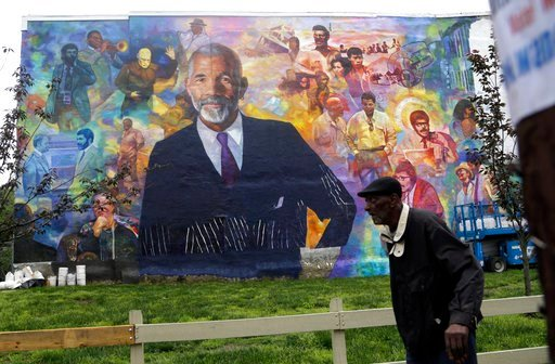 (AP Photo/Jacqueline Larma). A pedestrian walks past a mural of journalist Ed Bradley, Wednesday, May 16, 2018 in Philadelphia. The mural, by artist Ernel Martinez, is in the Belmont neighborhood of west Philadelphia where Bradley grew up. A free publi...