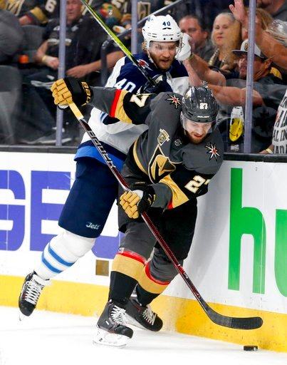 (AP Photo/John Locher). Vegas Golden Knights defenseman Shea Theodore, right, knocks the puck away from Winnipeg Jets right wing Joel Armia during the third period of Game 3 of the NHL hockey playoffs Western Conference finals Wednesday, May 16, 2018, ...