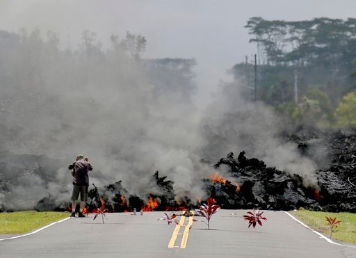 (AP Photo/Caleb Jones, File). FILE - In this May 5, 2018 file photo, offerings of ti leaves, rocks and cans to the fire goddess Pele, lie in front of lava as it burns across a road in the Leilani Estates subdivision as an unidentified person takes pict...