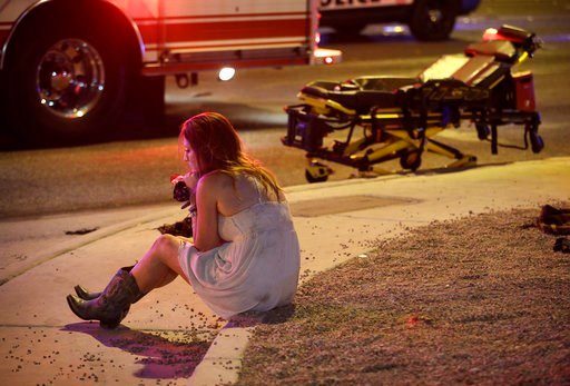 (AP Photo/John Locher,File). FILE - In this Oct. 2, 2017 file photo a woman sits on a curb at the scene of a shooting outside a music festival on the Las Vegas Strip. Police in Las Vegas plan to release witness statements and officer reports of the Oct...