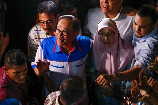 (AP Photo/Vincent Thian). Malaysia's reformist icon Anwar Ibrahim, left, arrive with his wife Wan Azizah, right, at a rally in Petaling Jaya, Malaysia, Wednesday, May 16, 2018. Anwar has been freed from custody after receiving a pardon from the king, p...