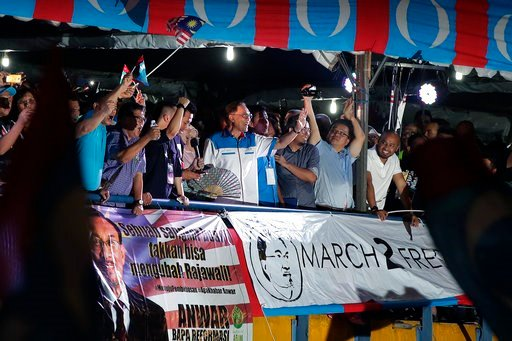 """(AP Photo/Andy Wong). Malaysia's reformist icon Anwar Ibrahim, center, gestures to his supporters during a rally in Petaling Jaya, Malaysia, Wednesday, May 16, 2018.  Reformist icon Anwar Ibrahim celebrated a """"new dawn"""" for Malaysia after he was given ..."""
