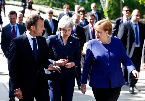 (AP Photo/Darko Vojinovic). German Chancellor Angela Merkel, right, speaks with French President Emmanuel Macron, left, and British Prime Minister Theresa May after meeting at a hotel on the sidelines of an EU-Western Balkans summit in Sofia, Bulgaria,...