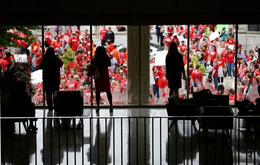 (AP Photo/Gerry Broome). People watch from inside the Legislative Building as participants gather during a teachers rally at the General Assembly in Raleigh, N.C., Wednesday, May 16, 2018. Thousands of teachers rallied the state capital seeking a polit...