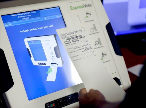 (AP Photo/David Goldman, File). FILE - This Oct. 19, 2017, file photo shows a new voting machine which prints a paper record on display at a polling site in Conyers, Ga. Georgia officials have estimated it could cost over $100 million to adopt the mach...