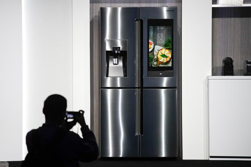 (AP Photo/Jae C. Hong, File). FILE- In this Jan. 8, 2018, file photo, an attendee takes pictures of the new Samsung Family Hub smart refrigerator during a news conference at CES International in Las Vegas.  Payment networks and manufacturers are buildi...