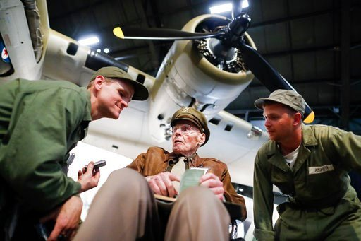 """(AP Photo/John Minchillo). United States Air Force (Ret.) Col. Howard Hunt, center, meets with Memphis Belle fans during the private viewing of the Boeing B-17 """"Flying Fortress"""" at the National Museum of the U.S. Air Force, Wednesday, May 16, 2018, in ..."""