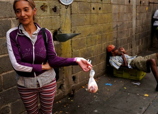 """(AP Photo/Fernando Llano). In this May 11, 2018 photo, Vaceliza Villa holds a bag of raw chicken skin in an outdoor market, as a boisterous electoral campaign marches past, in Caracas, Venezuela. """"I really don't care what happens on Sunday,"""" said Villa..."""
