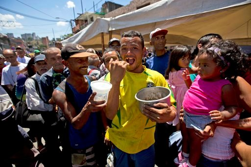 """(AP Photo/Fernando Llano). In this May 12, 2018 photo, a man holding an empty pot, shouts out, """"I am hungry"""" while standing in line to receive a free serving of soup at a campaign rally hosted by presidential candidate Javier Bertucci, in Caracas, Vene..."""