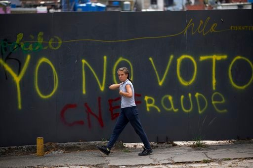 """(AP Photo/Fernando Llano). FILE - In this April 20, 2018 file photo, a pedestrian walks past graffiti spray-painted on a wall with a message that reads in Spanish: """"I won't vote"""", in Caracas, Venezuela. As Venezuela's presidential candidates make their..."""