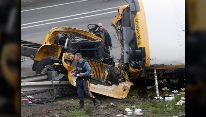 Emergency personnel work at the scene of a school bus and dump truck collision, injuring multiple people, on Interstate 80 in Mount Olive, N.J., on Thursday. (AP Photo/Seth Wenig)