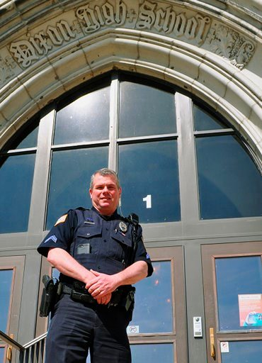 (City of Dixon via AP). In this undated photo provided by City of Dixon, police officer Mark Dallas poses for a photo in front of Dixon High School in Dixon, Ill. Dallas, a school resource officer at the northern Illinois high school, was hailed as a h...