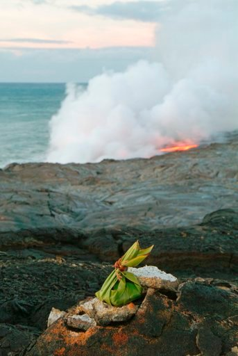 (AP Photo/David Jordan, File). FILE - In this June 22, 2004 file photo, an offering to Pele, goddess of Hawaiian volcanoes, adorns the cliffs above the newest lava flow from Kilauea volcano as it enters the Pacific Ocean at dawn in Volcano, Hawaii. Whe...