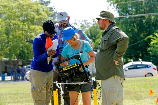 (AP Photo/Gerald Herbert). Davette Gadison, left, bio archeology grad student at Tulane University, and Andy Schroll, archeology grad student, behind, look over data with Dr. Cynthia Ebinger and Dr. Ryan Gallacher, in Thibodaux, La., Thursday, May 17, ...