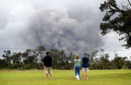 (AP Photo/Caleb Jones). People watch as ash rises from the summit crater of Kilauea volcano, Thursday, May 17, 2018, in Volcano, Hawaii.