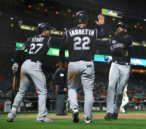 (AP Photo/Ben Margot). Colorado Rockies' Charlie Blackmon, right, celebrates with Trevor Story (27) and Chris Iannetta (22) after scoring against the San Francisco Giants in the 12th inning of a baseball game Thursday, May 17, 2018, in San Francisco.