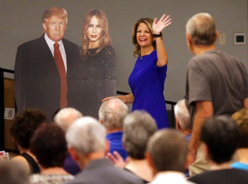 (AP Photo/Matt York). In this Tuesday, May 8, 2018 photo, U.S. Senatorial candidate Kelli Ward waves to volunteers and voters as she walks past a cardboard cut-out of President Donald Trump and the first lady Melania Trump during the Sun Lakes Republic...