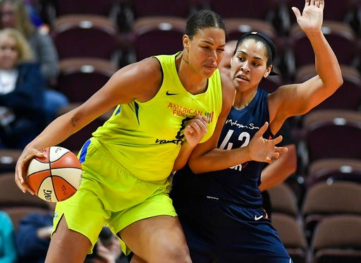 (AP Photo/Jessica Hill, File). FILE - In this May 8, 2018, file photo, Dallas Wings' Liz Cambage, left, drives against Connecticut Sun's Brionna Jones during a preseason WNBA basketball game in Uncasville, Conn. Cambage is coming back to the WNBA after...