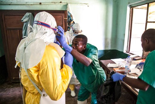 (Mark Naftalin/UNICEF via AP). In this photo taken Saturday, May 12, 2018, health workers don protective clothing as they prepare to attend to patients in the isolation ward to diagnose and treat suspected Ebola patients, at Bikoro Hospital in Bikoro, ...