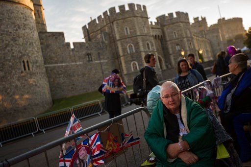 (AP Photo/Emilio Morenatti). A woman sits after spending the night in front of Windsor castle, England, Friday, May 18, 2018. Preparations continue in Windsor ahead of the royal wedding of Britain's Prince Harry and Meghan Markle Saturday May 19.