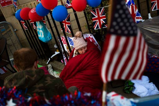 (AP Photo/Emilio Morenatti). A woman spends the night near Windsor castle, England, Friday, May 18, 2018. Preparations continue in Windsor ahead of the royal wedding of Britain's Prince Harry and Meghan Markle Saturday May 19.