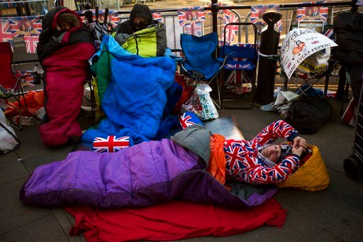 (AP Photo/Emilio Morenatti). A man sleeps on the ground, spending the night near Windsor castle, England, Friday, May 18, 2018. Preparations continue in Windsor ahead of the royal wedding of Britain's Prince Harry and Meghan Markle Saturday, May 19.