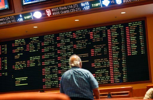 (AP Photo/John Locher, File). FILE - In this Monday, May 14, 2018 file photo, betting odds are displayed on a board in the sports book at the South Point hotel and casino in Las Vegas. A new poll finds that half of Americans approve of legal sports bet...