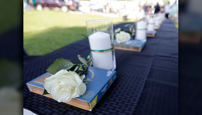 Ten candles, roses and Bibles are displayed on a table during a prayer vigil following a shooting at Santa Fe High School in Santa Fe, Texas, on Friday, May 18, 2018. (AP Photo/David J. Phillip)