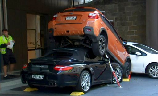 (Australian Broadcasting Corp. via AP). In this image made from video, a Porsche Carrera car is underneath another car in Sydney, Australia Thursday, May 31, 2018. Australian media say a valet drove the soft-top Porsche Carrera under another vehicle Th...