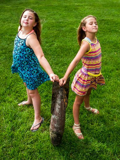 (Jake May/The Flint Journal via AP). In this Wednesday, May 30, 2018 photo, Paige Burnett, 10, left, and Sage Menzies, 9  pose with a World War I practice bomb they discovered the day before while swimming in Lobdell Lake behind the Menzies' home in Li...