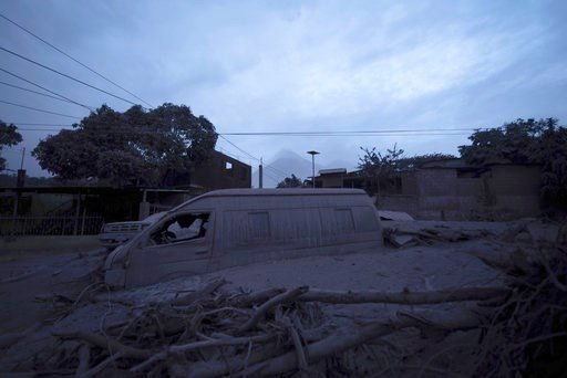 """(AP Photo/Santiago Billy). A vehicle sits partially buried in volcanic ash spewed by the Volcan de Fuego, or """"Volcano of Fire,"""" pictured in background, in Escuintla, Guatemala, early Monday, June 4, 2018. A fiery volcanic eruption in south-central Guat..."""