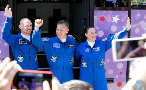 (AP Photo/Dmitri Lovetsky). U.S. astronaut Serena Aunon-Chancellor, right, Russian cosmonaut Sergey Prokopyev, centre, and German astronaut Alexander Gerst, members of the main crew to the International Space Station (ISS), wave near a bus from a hotel...
