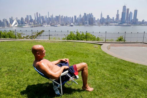 (AP Photo/Seth Wenig). FILE - In this Tuesday, May 15, 2018 file photo, Rick Stewart sits in the sunshine with the New York City skyline in the background, in a park in Weehawken, N.J. According to weather records released on Wednesday, June 6, 2018, M...