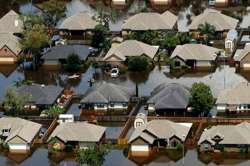 (AP Photo/Charlie Riedel). FILE - In this Friday, Sept. 1, 2017 file photo, homes are surrounded by water from the flooded Brazos River in the aftermath of Hurricane Harvey in Freeport, Texas. According to a study released on Wednesday, June 6, 2018, t...
