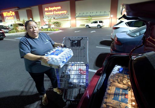 (Mark Ylen/Albany Democrat-Herald via AP). In this photo taken May 29, 2018, Juana Francisco loads her trunk with water purchased at WinCo. Officials in Salem, Ore., re-issued a limited no-drink warning Wednesday, June 6, 2018, for tap water in the sta...