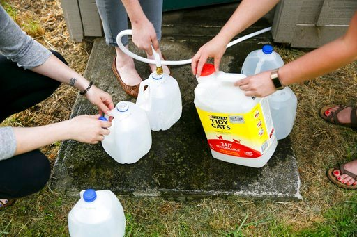 (Molly J. Smith/Statesman-Journal via AP). In this photo taken May 30, 2018,  Willamette Humane Society staff members fill containers with well water from the shelter's pump house in Salem, Ore. Officials in Salem, Ore., re-issued a limited no-drink wa...