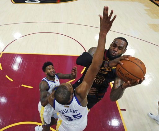 (Gregory Shamus/Pool Photo via AP). Cleveland Cavaliers' LeBron James shoots over Golden State Warriors' Kevin Durant during the first half of Game 3 of basketball's NBA Finals, Wednesday, June 6, 2018, in Cleveland.