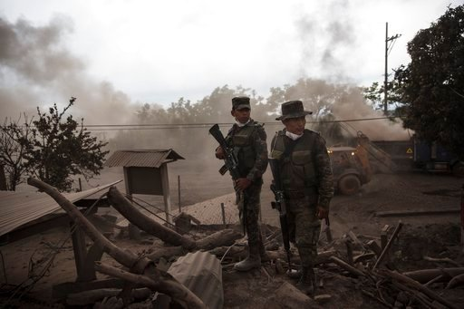 """(AP Photo/Rodrigo Abd). Soldiers stand guard outside a destroyed home in the disaster zone covered in volcanic ash near the Volcan de Fuego, or """"Volcano of Fire, in the El Rodeo hamlet of Escuintla, Guatemala, Wednesday, June 6, 2018. Firefighters said..."""