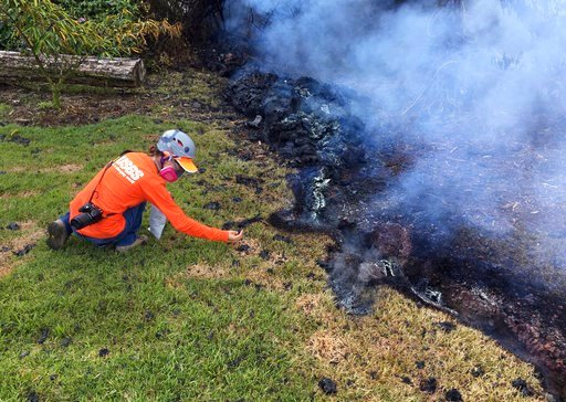 (U.S. Geological Survey via AP, File). FILE - In this May 6, 2018, file photo provided by the U.S. Geological Survey, a Hawaii Volcano Observatory (HVO) geologist collects samples of spatter for laboratory analysis in the Leilani Estates subdivision ne...