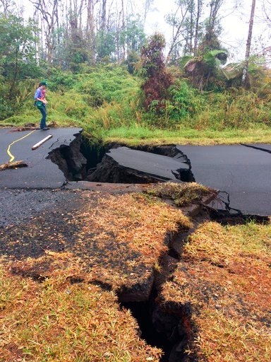 (U.S. Geological Survey via AP, File). FILE - In this May 17, 2018, file photo released by the U.S. Geological Survey, a Hawaiian Volcano Observatory, HVO geologist monitors the the vertical offset across the cracks on Nohea Street in Leilani Estates i...