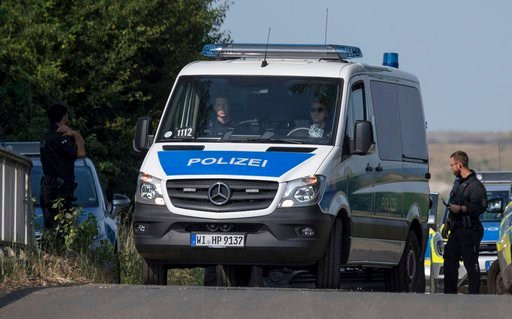 (Foto: Boris Roessler/dpa via AP). Police officers block a road near Wiesbaden, Germany, Thursday, June 7, 2018. The body of the 14-year-old girl, who had been missing since May 22, was found Wednesday on the outskirts of Wiesbaden.