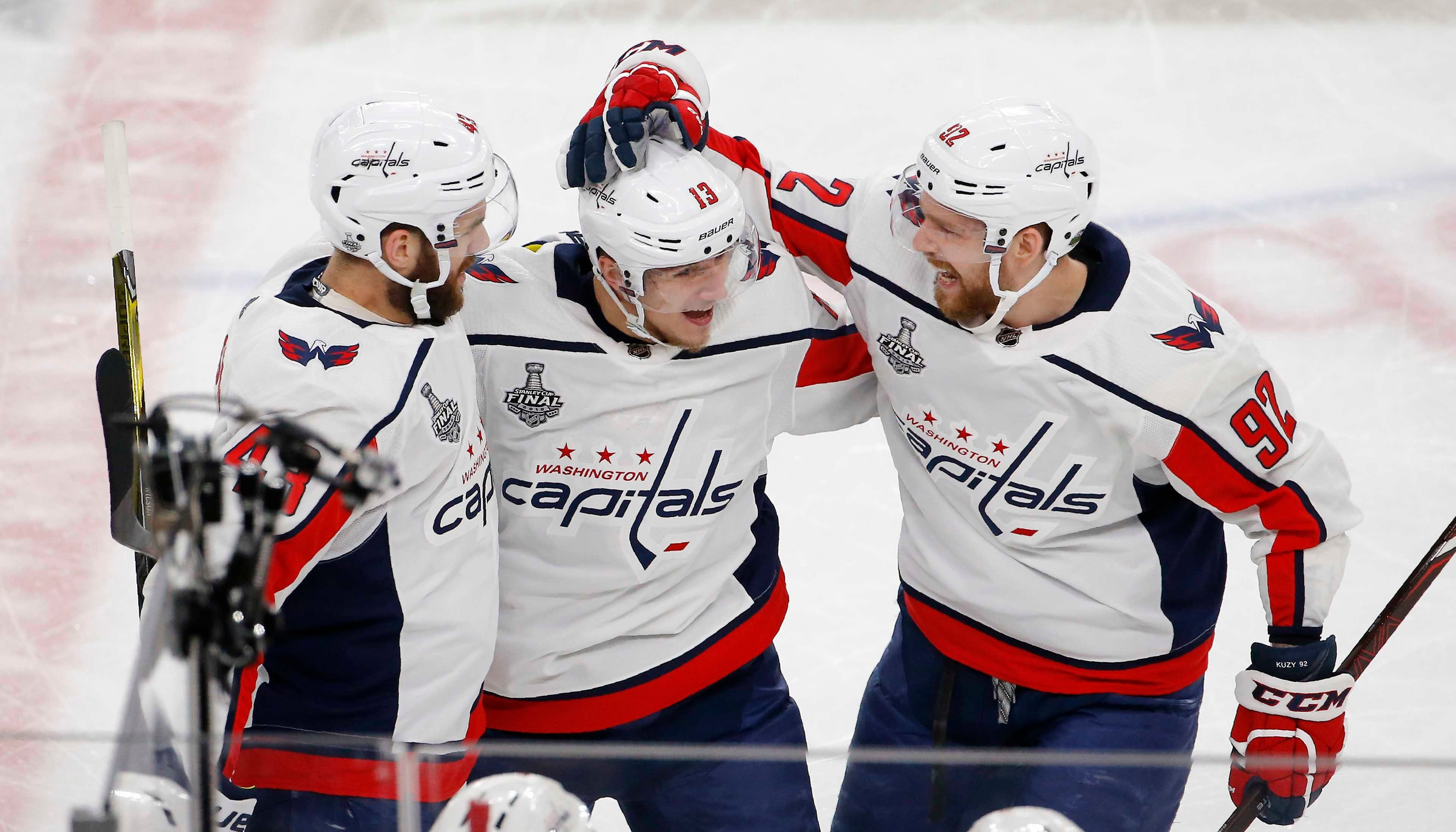 Washington Capitals left wing Jakub Vrana, center, celebrates his goal with right wing Tom Wilson, left, and center Evgeny Kuznetsov during the second period in Game 5 of the NHL hockey Stanley Cup Finals. (AP Photo/Ross D. Franklin)