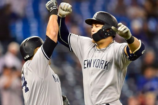 (Frank Gunn/The Canadian Press via AP). New York Yankees' Giancarlo Stanton, right, celebrates his home run against the Toronto Blue Jays during the 13th inning of a baseball game Wednesday, June 6, 2018, in Toronto.