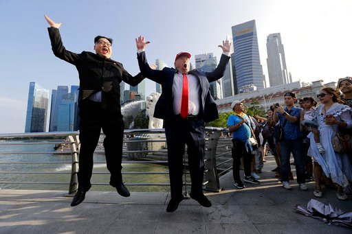(AP Photo/Wong Maye-E). Kim Jong Un and Donald Trump impersonators, Howard X, left, and Dennis Alan, second left, pose for photographs during their visit to the Merlion Park, a popular tourist destination in Singapore, on Friday, June 8, 2018. Kim Jong...